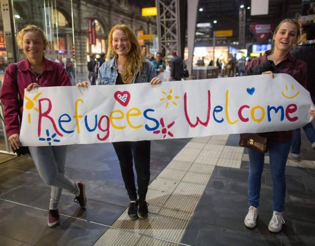 Girls-standing-with-sign-welcoming-migrants-70132-618x482.jpg