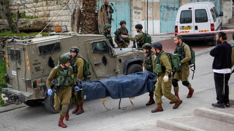 Israeli soldiers remove the body of a Palestinian man shot after he stabbed and wounded a soldier in the West Bank city of Hebron on March 24, 2016..jpg
